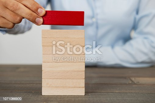 Business woman building up wood tower.