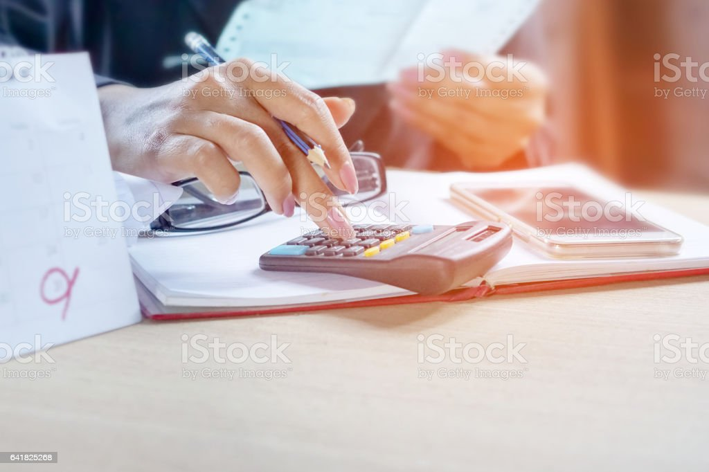 a business woman hand calculating her monthly bills with calendar and...