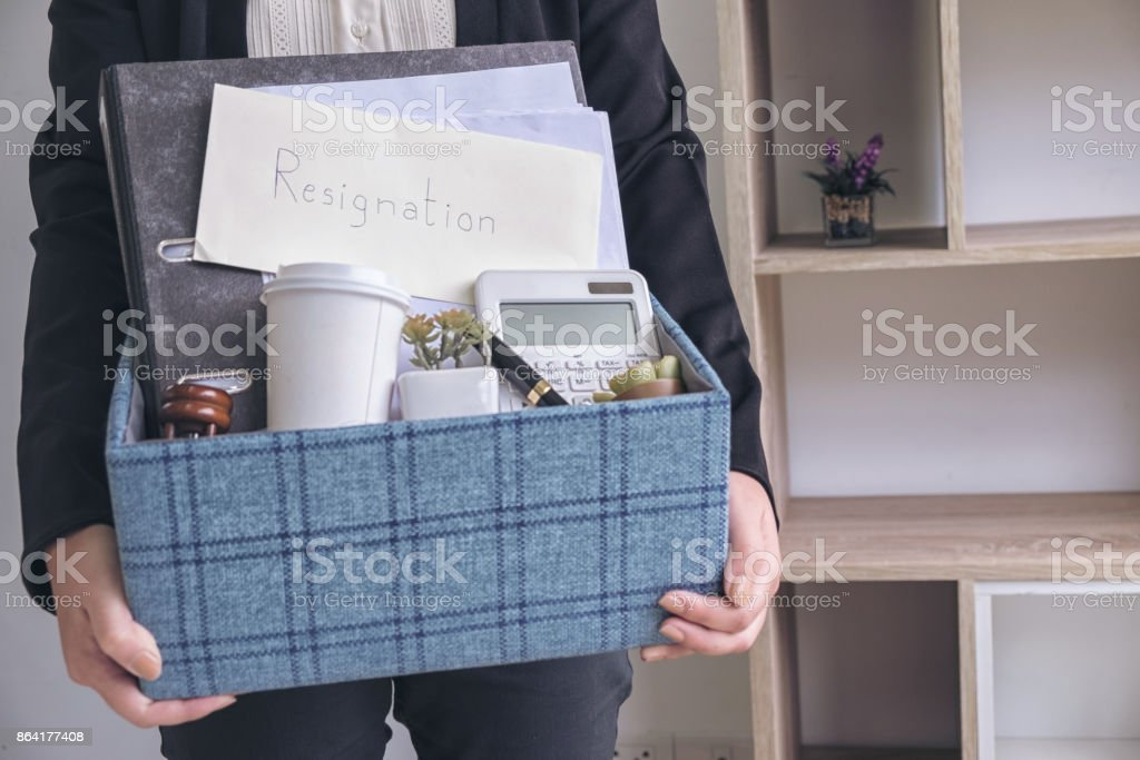 business woman carrying packing up all his personal belongings and files into a brown cardboard box to resignation in modern office, resign concept royalty-free stock photo
