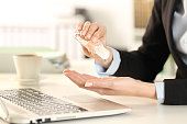 istock Business woman cleaning hands with sanitizer in the office 1216080981