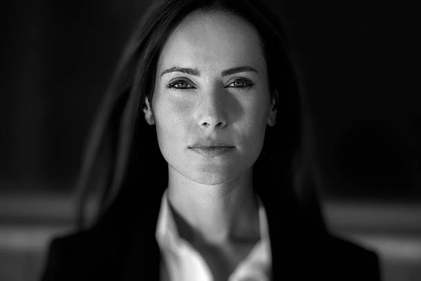 Business woman close up Business woman in suit outfit close up portrait, in front of a blurry background monochrome stock pictures, royalty-free photos & images