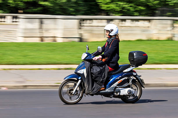 Business woman commuting Paris, France - April 15, 2014: Business woman travelling to work on a scooter in Paris, France, on April 15, 2014 three wheel motorcycle stock pictures, royalty-free photos & images
