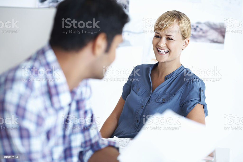 Business woman conversing with male associate stock photo