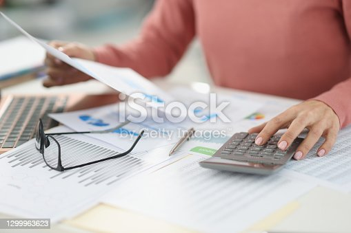 Business woman counting on calculator and holding documents in hands closeup. Bookkeeping concept