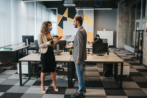 Young business woman in modern office avoiding handshake and criticizes her colleague's irresponsible behavior not wearing a mask and trying to shake hands