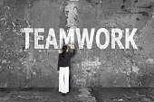 istock business woman drawing teamwork on wall 518200659