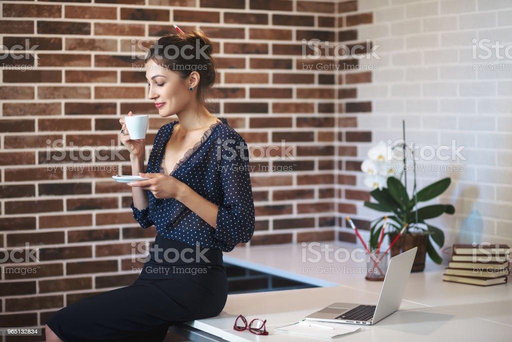Business woman drinking coffe in the office zbiór zdjęć royalty-free