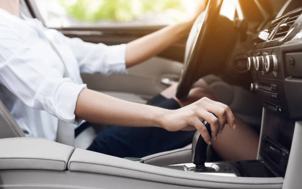 Business woman driver shifting automatic transmission and driving Business woman driving and shifting automatic transmission, side view gearshift stock pictures, royalty-free photos & images