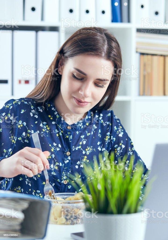 Kobieta biznesu jedzenie lunch w jej miejscu pracy patrząc na ekranie laptopa. Foldery z dokumentami na pierwszym planie. Koncepcja Dedline - Zbiór zdjęć royalty-free (Biurko)
