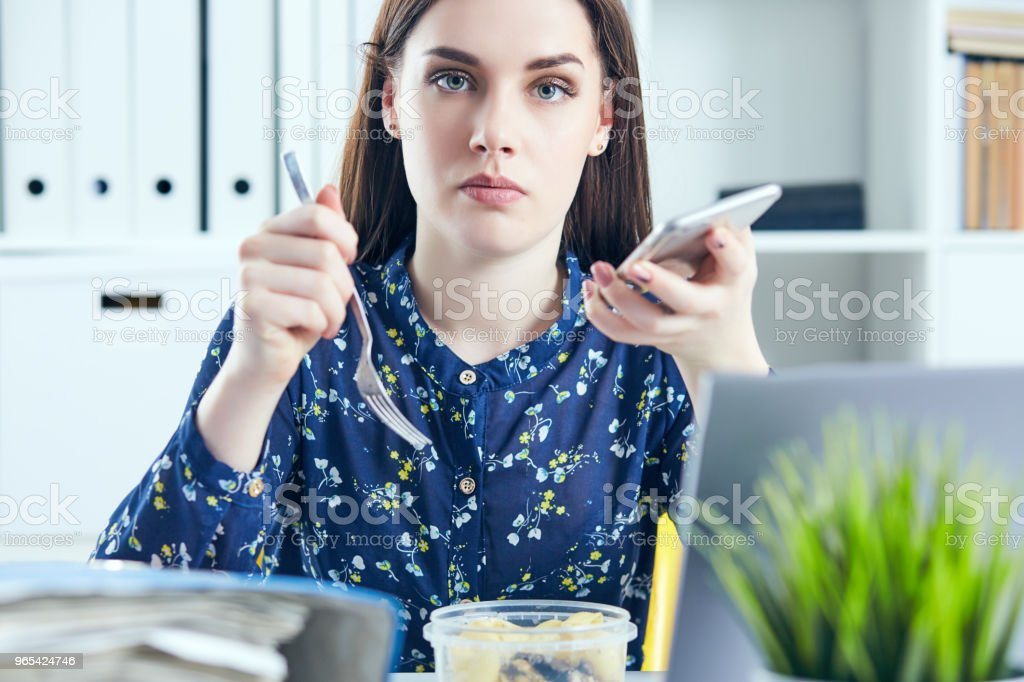 Business woman eating lunch at her workplace looking at the laptop screen. Folders with documents in the foreground. Dedline concept royalty-free stock photo