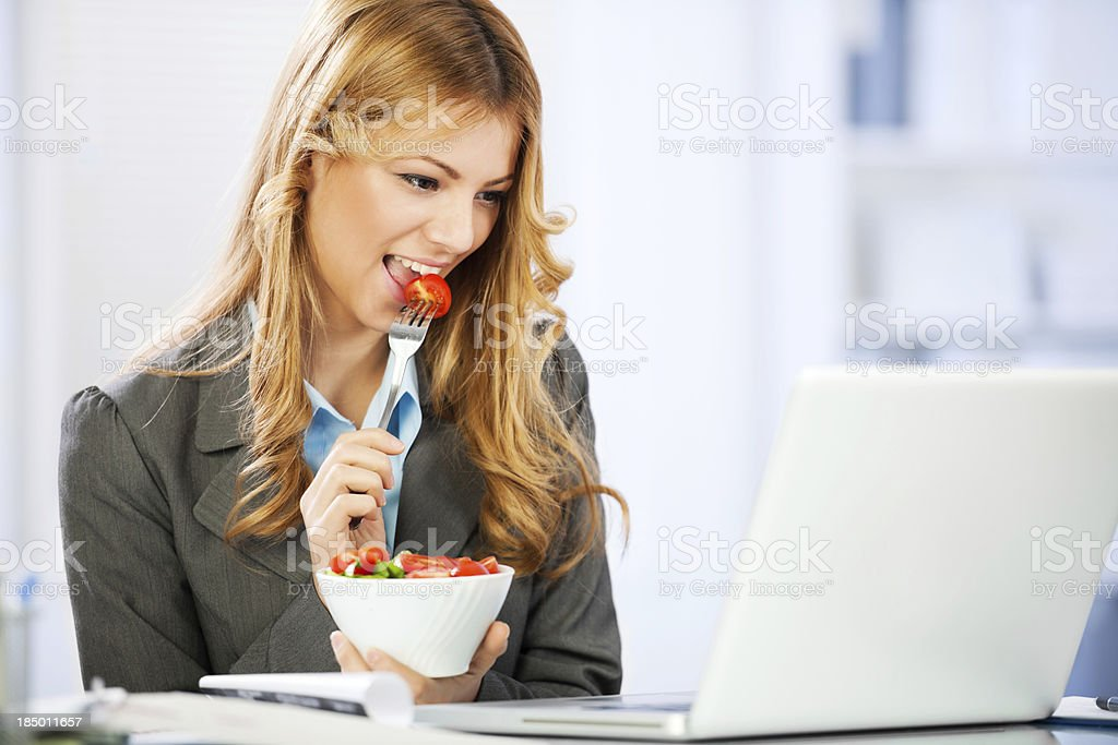Business woman eating salad and using laptop. royalty-free stock photo