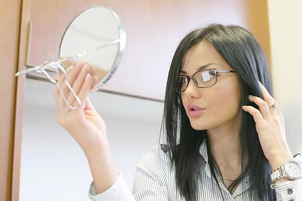 business woman examining her hair - frisuren 2016 frauen stock-fotos und bilder