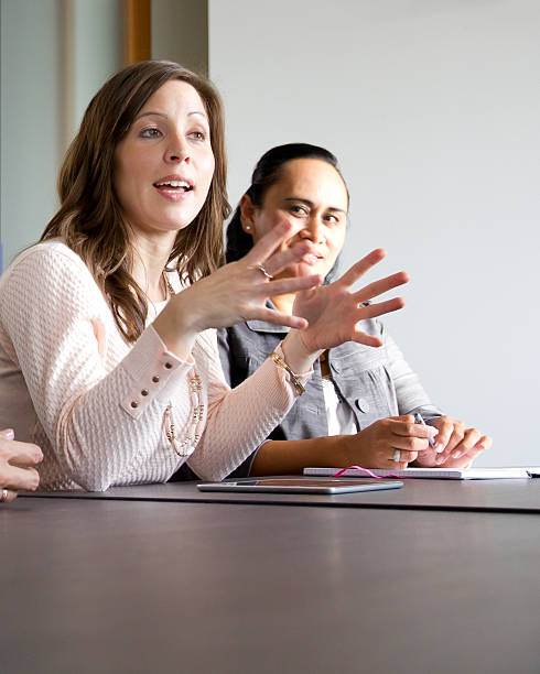 Business woman explaining strategy to team in boardroom meeting - foto de stock