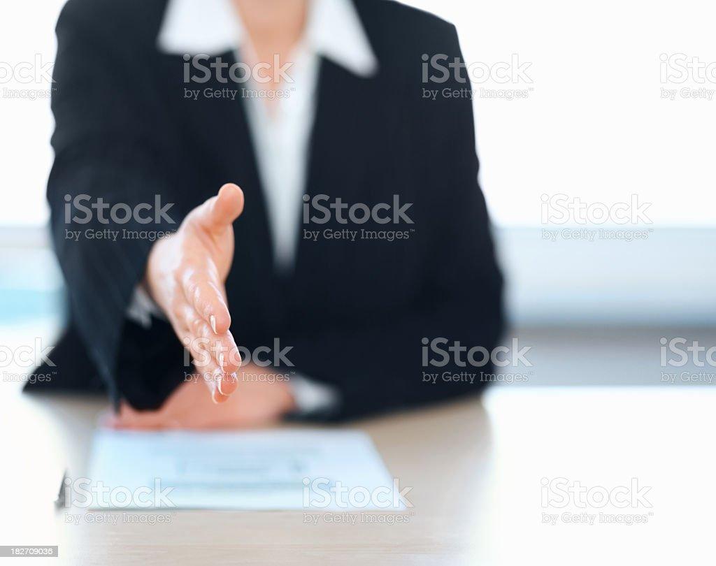 Business woman extending a handshake during an interview stock photo