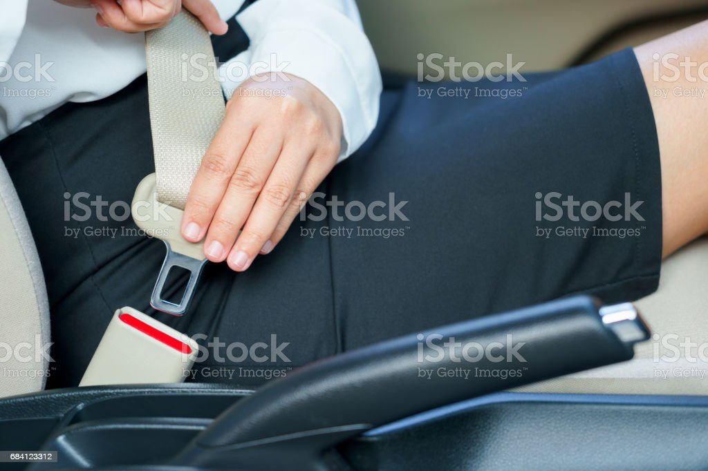 Business woman fastening seat belt in car before driving. royaltyfri bildbanksbilder