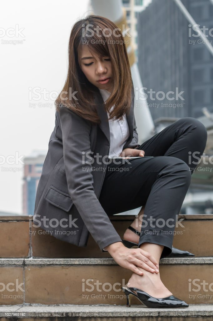 Business woman feeling pain in the ankle. stock photo
