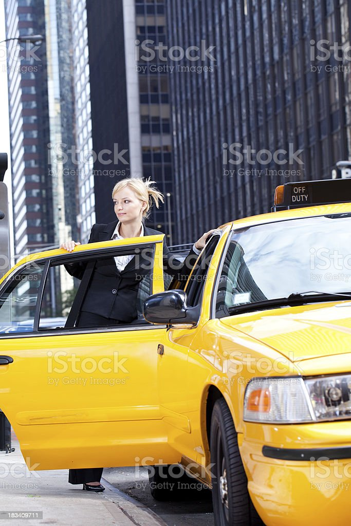 Business woman getting into yellow taxi cab royalty-free stock photo