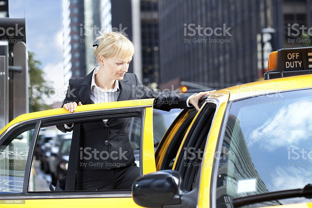 Business woman getting into yellow taxi royalty-free stock photo
