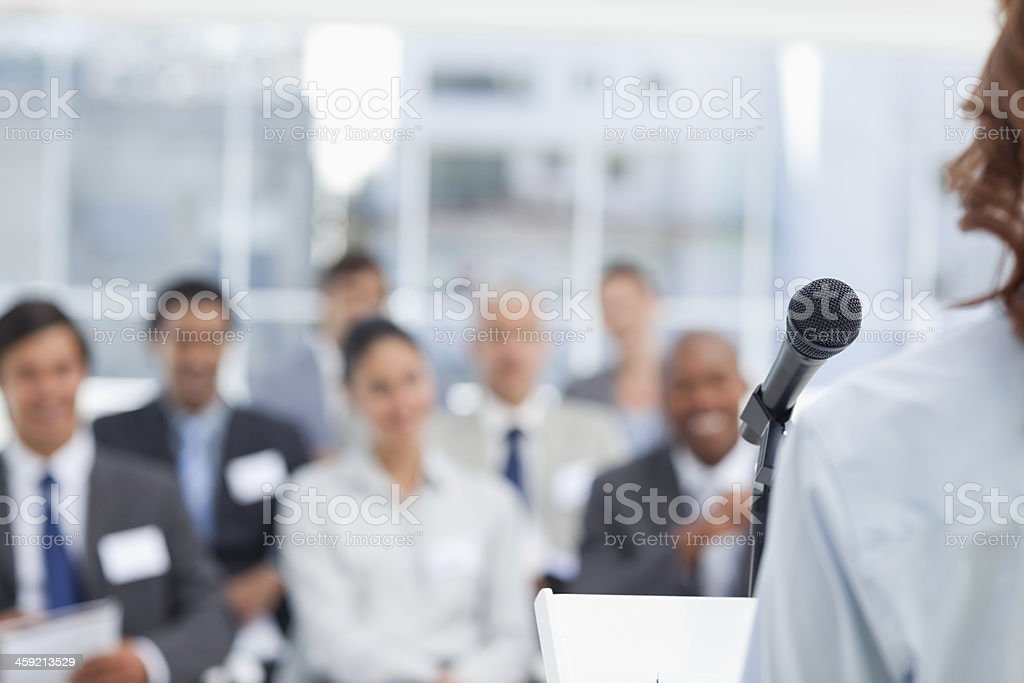 Business woman giving a speech while her colleagues are watching stock photo
