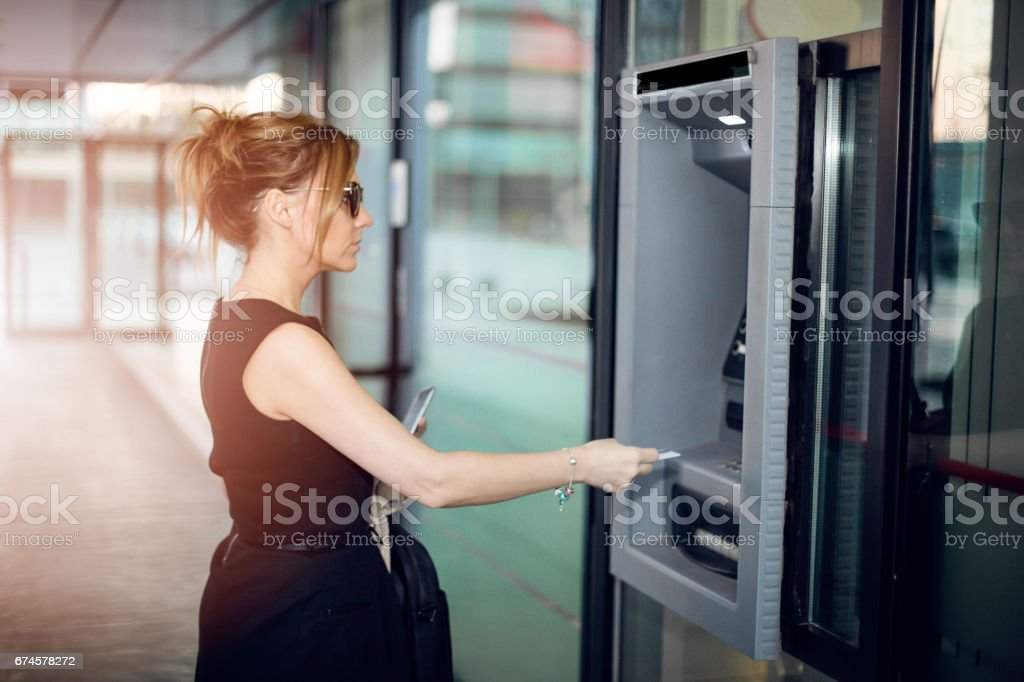 Business woman going to the ATM stock photo