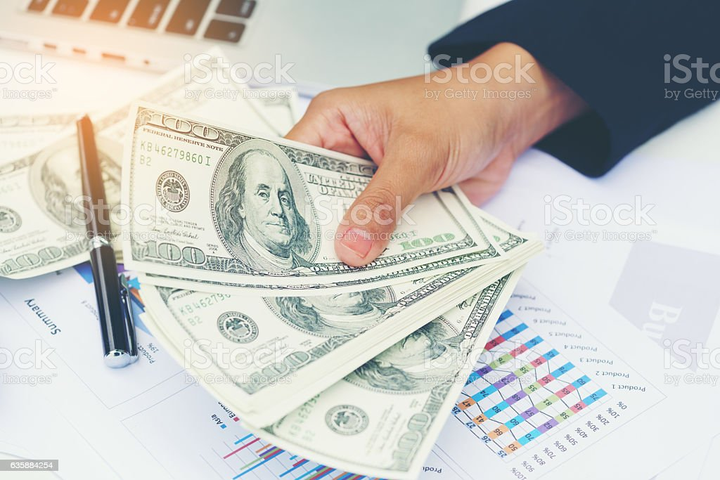 Business woman gripping dollar bills in her hand stock photo