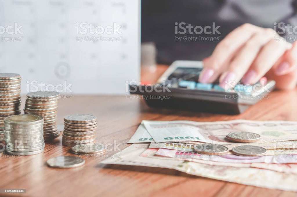 business woman hand calculating her monthly expenses that including...