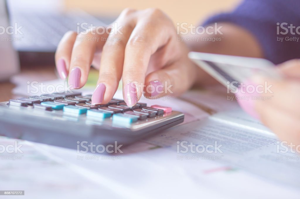 business woman hand counting on calculator using her credit card stock photo