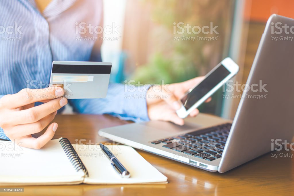 Business woman hand holds a credit card and uses a telephone to shop online. - Royalty-free Adult Stock Photo