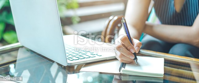 Business woman hand is writing on a notepad with a pen and using a laptop computer.Web banner.