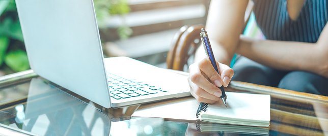 istock Business woman hand is writing on a notepad with a pen and using a laptop computer. 1098154178