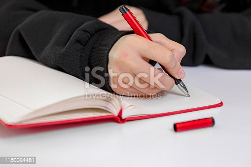Business woman hand is writing on notepad with pen in office.