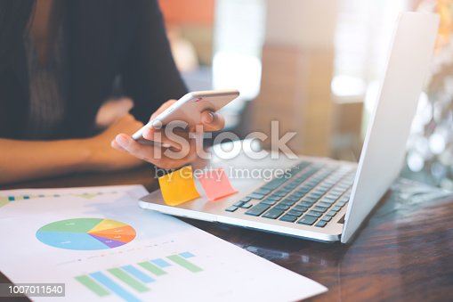 996183898 istock photo Business woman hand uses a phone to work on charts and graphs that show results. 1007011540