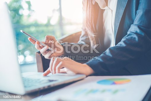 996183898 istock photo Business woman hand uses a phone to work on charts and graphs that show results. 1057416482