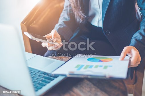 996183898 istock photo Business woman hand uses a phone to work on charts and graphs that show results. 1057416486