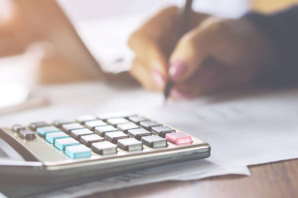 business woman hand woman hand calculating her monthly expenses with calculator in foreground blur background business woman hand woman hand calculating her monthly expenses with calculator in foreground fee stock pictures, royalty-free photos & images