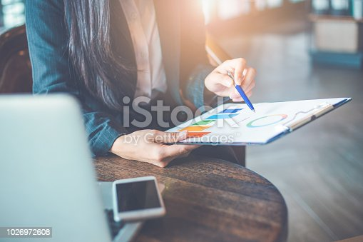 996183898 istock photo Business woman hand work on charts and graphs that show results.She uses the pen to point to the graph. 1026972608