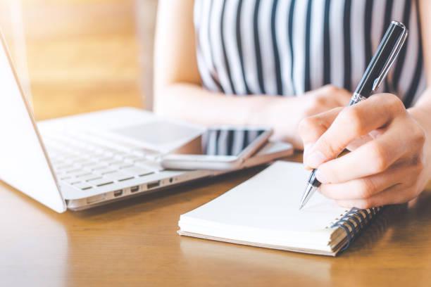 unternehmen frau hand arbeit am computer und schreiben auf ein noteped mit einem stift im büro. - checkliste stock-fotos und bilder