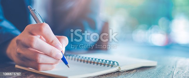 Business woman hand  writing on a notepad with a pen in the office.Web banner.