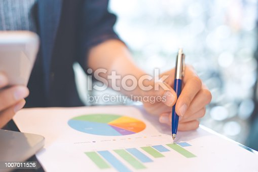 996183898 istock photo Business woman hand writing on charts and graphs that show results. 1007011526