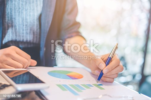 996183898 istock photo Business woman hand writing on charts and graphs that show results. 1015188796