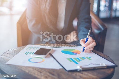 996183898 istock photo Business woman hand writing on charts and graphs that show results. 1023272614