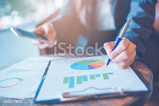 996183898 istock photo Business woman hand writing on charts and graphs that show results. 1023272620