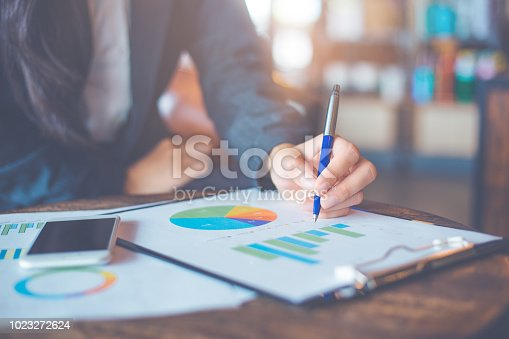 996183898 istock photo Business woman hand writing on charts and graphs that show results. 1023272624