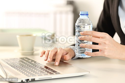 Close up of business woman hands holding bottled water on a desk at the office