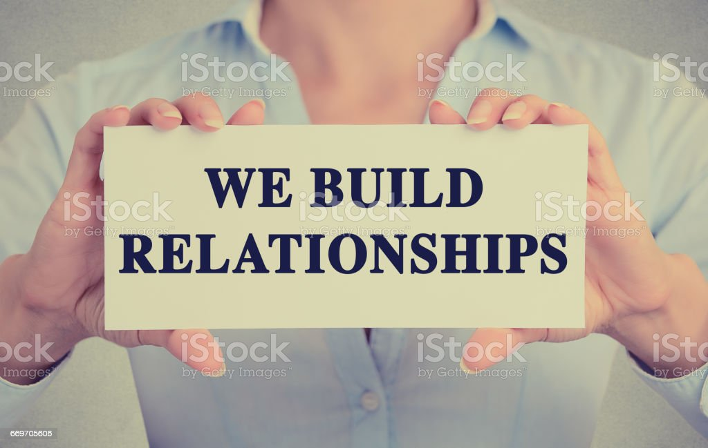business woman hands holding white card sign with we build relationships text message stock photo