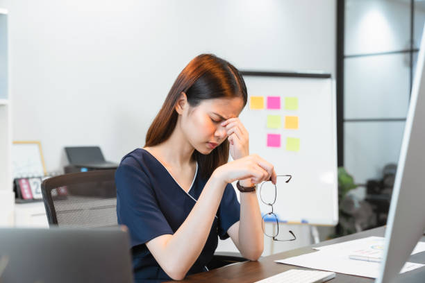 Business woman hands touching on the eyes due to tiredness from working computer for a long time, may be the cause of office syndrome. stock photo