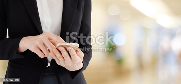 istock Business woman hands using smart phone over blur office with bokeh light background, banner, business on phone 699767236