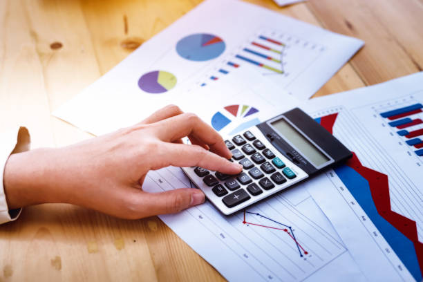 business woman hands working using calculator with financial data analyzing hand calculate writing and counting in office. Workplace strategy Concept. stock photo
