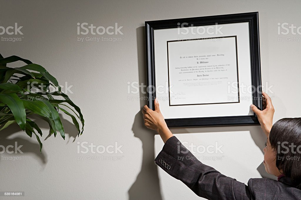 Business woman hanging framed certificate stock photo