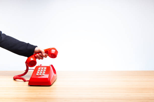 business woman hanging up old red telephone - squillare foto e immagini stock